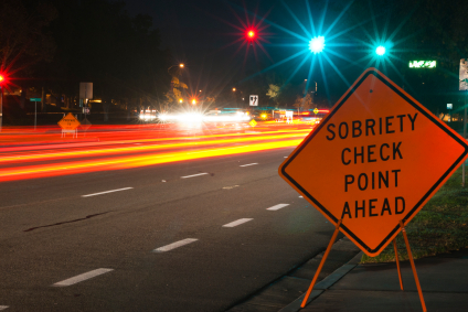 Sobriety checkpoint sign with vehicle light trails approaching on road